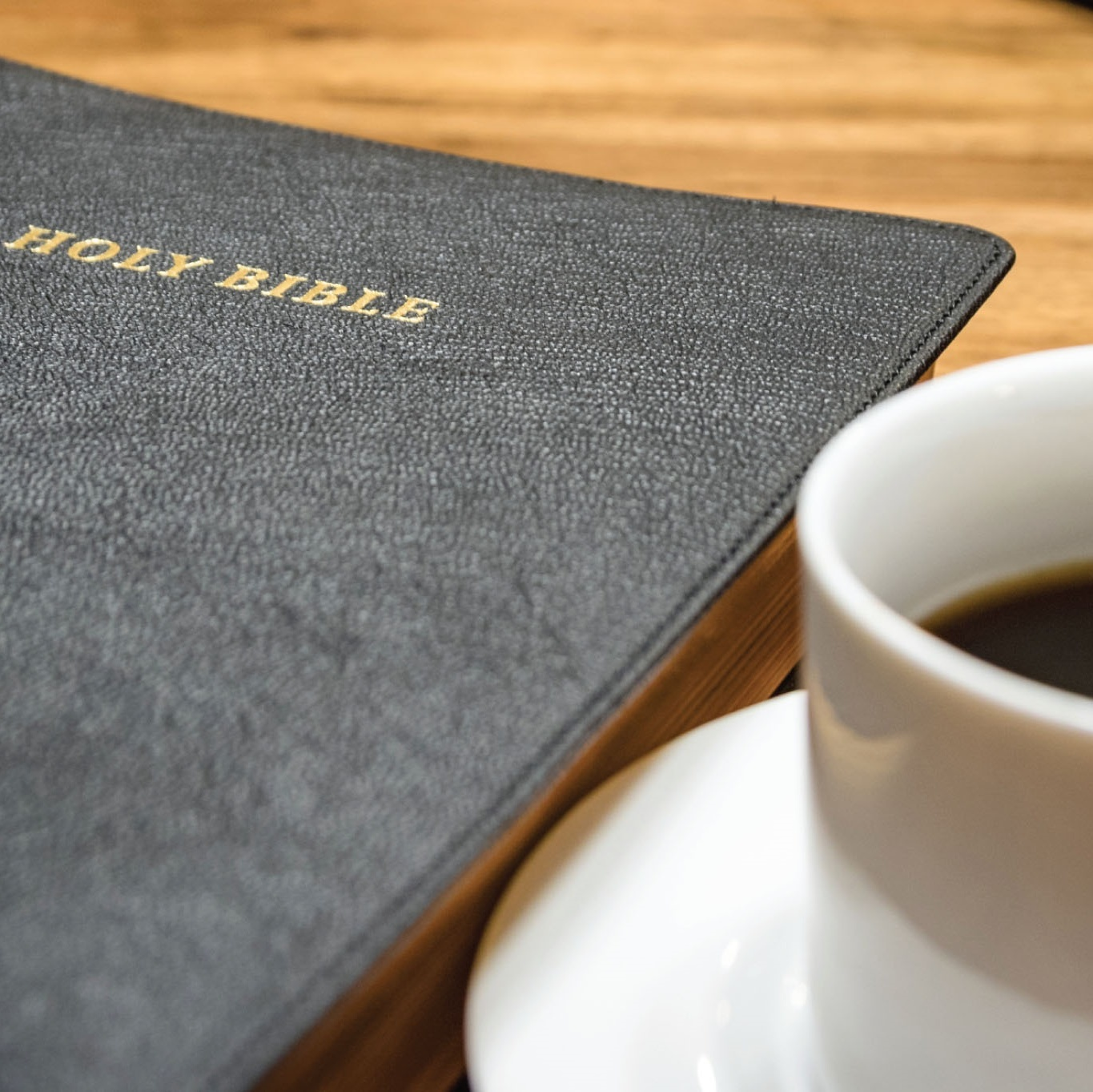 A cup of coffee next to the Bible.