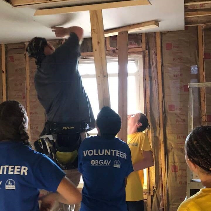 Youth leader with four youth hanging ceiling drywall during work camp